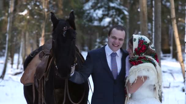 Newlyweds in the winter forest with a horse at sunset