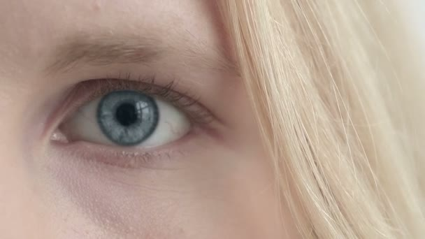 Eye of blonde girl changes color. Close up half of the face