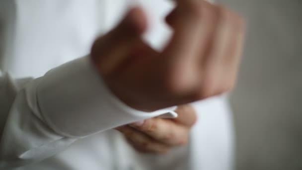 Muži nosí bílé košile a manžetové knoflíčky