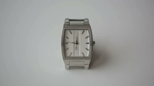 Silver wristwatch on a white background. Time lapse