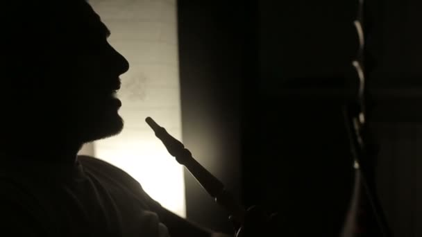 SLOW MOTION: Shadow of a man smoking a hookah.