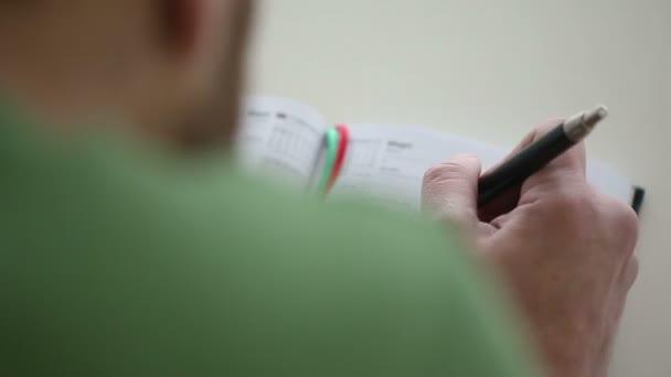Közelkép a kezében tollat írja a notebook