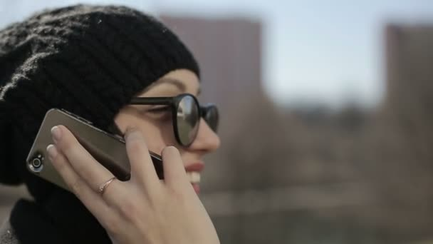 Young girl in sunglasses speaks by phone. Slow motion