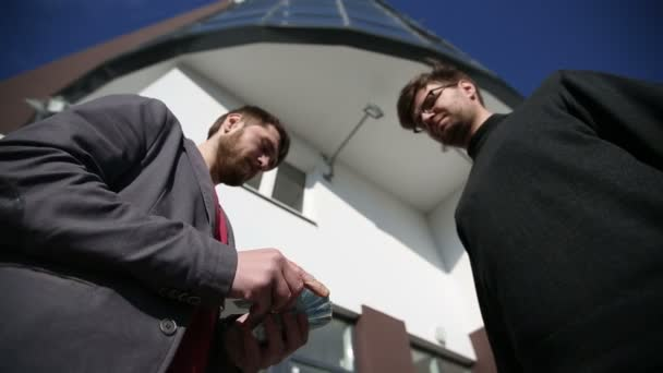Muži vzájemně předávat peníze eurobankovek a potřást rukou