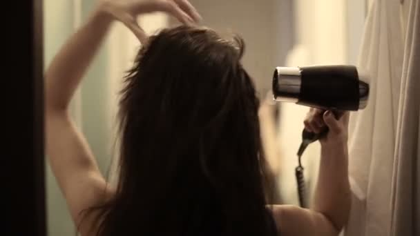 mladá žena sušení její vlasy se sušičkou