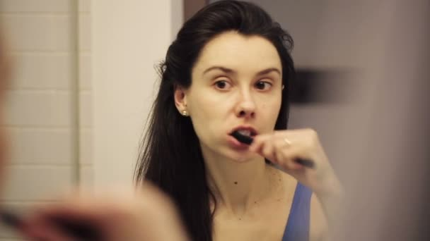 Young woman brushing teeth in bathroom of the hotel for checkout