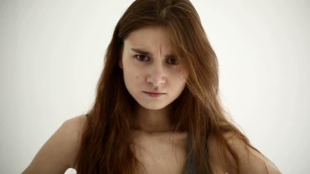 Překvapený mladá dívka na bílém pozadí. Zpomalený pohyb