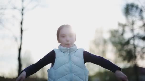 kleines Mädchen beim Seilspringen bei Sonnenuntergang. Zeitlupe