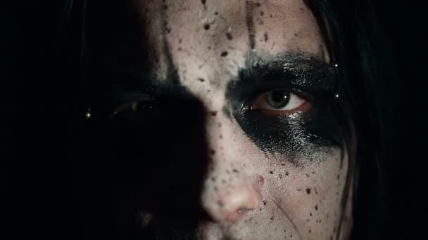 Zpěvák black metalové kapely. Zblízka do tváře na tmavém pozadí