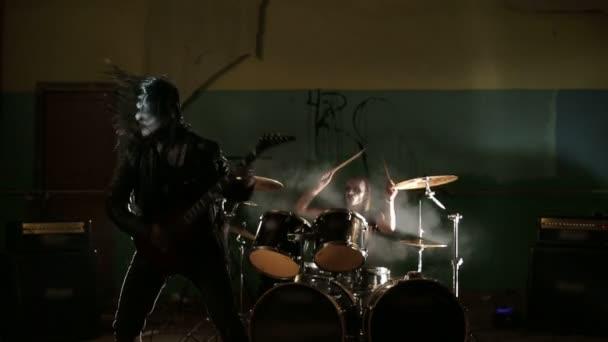 Zpěvák a dreummer black metalové kapely na tmavém pozadí