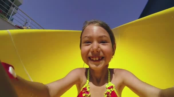 Child sliding down water slide in pool. Close up