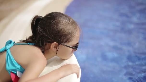 Dítě leží na lehátku u bazénu v hotelu