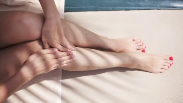 Donna sexy attraente il lettino vicino alla piscina che applica la crema solare sul suo corpo