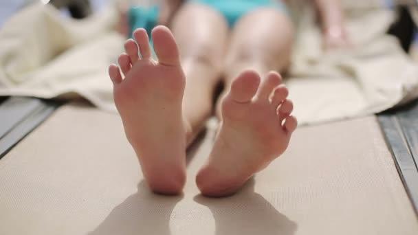 Dítě leží na lehátku u bazénu v hotelu a její nohy se pohybuje