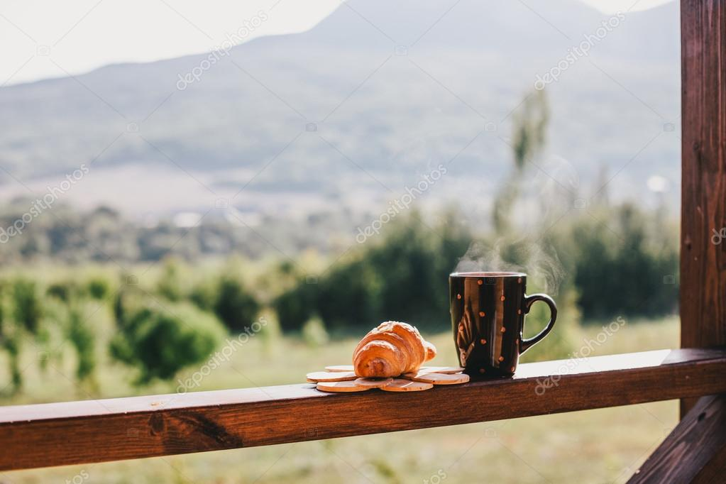 Cup of hot tea and croissant on balcony with mountains behind