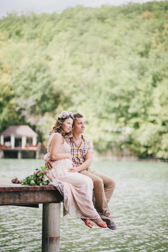 Young pregnant woman in a pink dress standing on a berth near lake with her husband