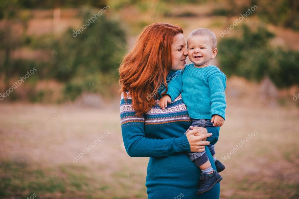Mother and her little son in a knitwear have a walk in a forest