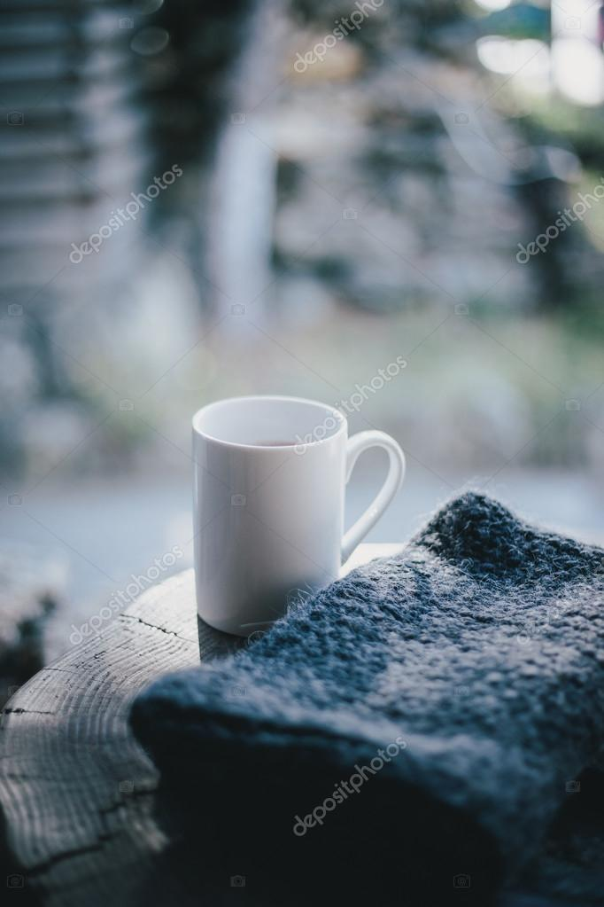 White mug with cocoa standing on a balcony