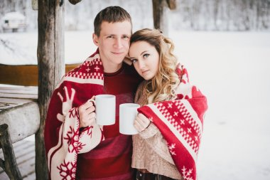 Happy couple wrapped in plaid drink hot tea in a snowy forest