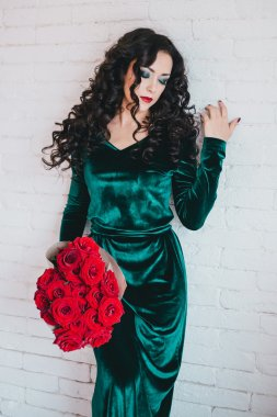 Beautiful woman in a green dress and red shoes with red roses
