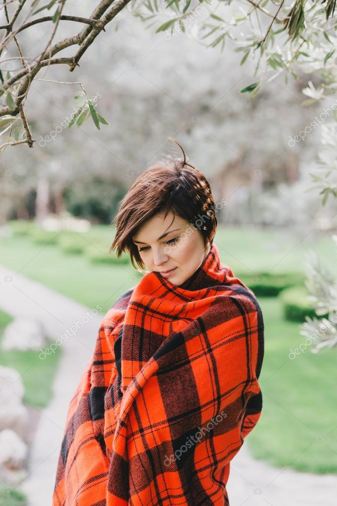 Pretty young woman with short haircut standing in a park wrapped in a warm blanket