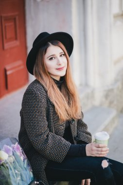 Pretty young woman in hat posing with coffee and flowers in bag