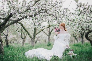 Beautiful bride in a vintage wedding dress posing in a blooming apple garden
