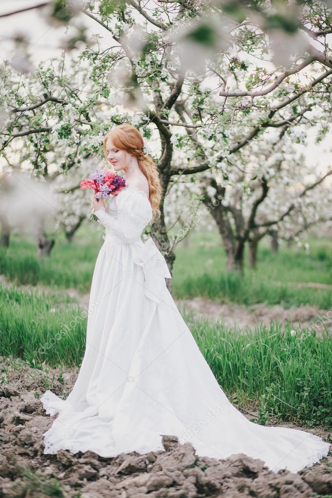 Beautiful bride in a vintage wedding dress posing in a blooming apple garden