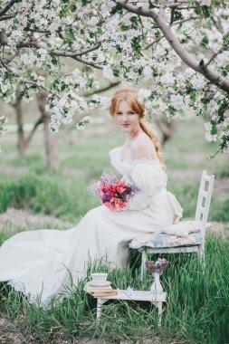 Beautiful bride in a vintage wedding dress posing in a garden