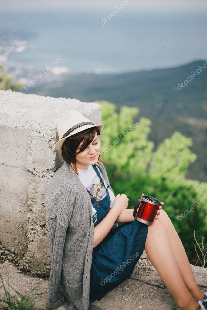 Young fashion woman sitting on a top of the mountain drinking tea