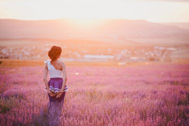 Young woman with beautiful hair standing in a lavender field at the sunset