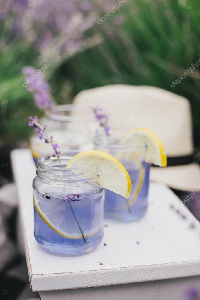 Homemade lavender lemonade with fresh lemons on a white wooden tray