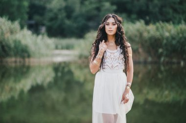Beautiful young woman with long curly hair in boho style dress posing near lake