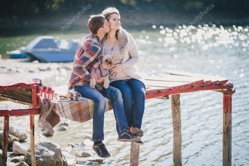 Young future parents and their dog in a funny costume sitting on a wooden bridge and having picnic near lake