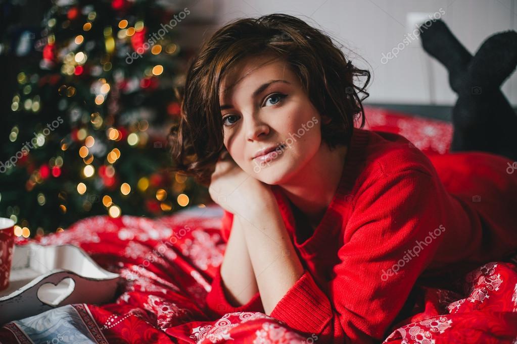 Rode Tricot Jurk.Jonge Vrouw In Een Rode Tricot Jurk Liggend Op Het Bed In De