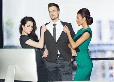Man in suit with two attractive women in office