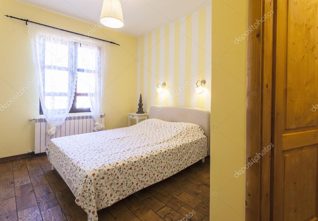 Interno di una semplice camera da letto con le pareti gialle — Foto ...