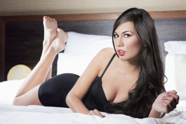 Seductive woman posing on bed in black lingerie