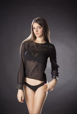 Young woman posing in see-through black blouse and panties