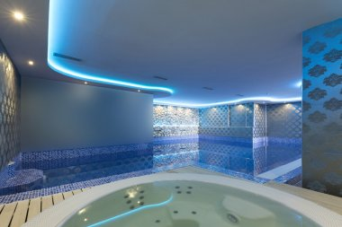 Indoors pool and jacuzzi with colorful lights at spa center