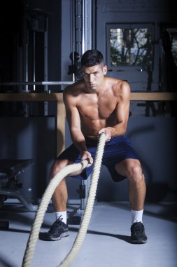 Muscular man in gym with battle ropes