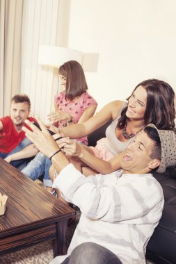 Couple hanging out with friends and fighting over remote control