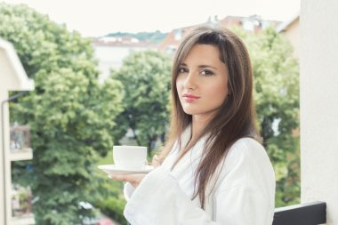 Beautiful young woman enjoying cup of coffee at the balcony
