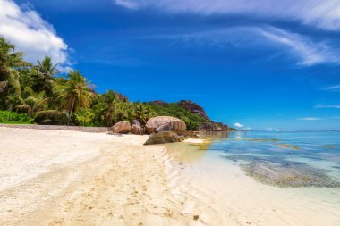 Beautiful beach with granite rocks and palms at Seychelles, La Digue.