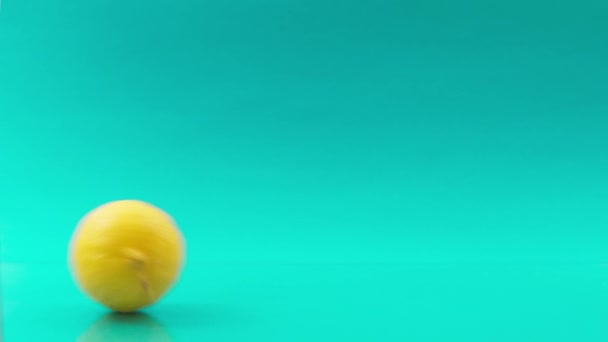rolling lemons one after one on turquoise background
