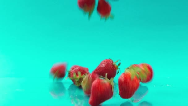 falling strawberry one after one on turquoise background