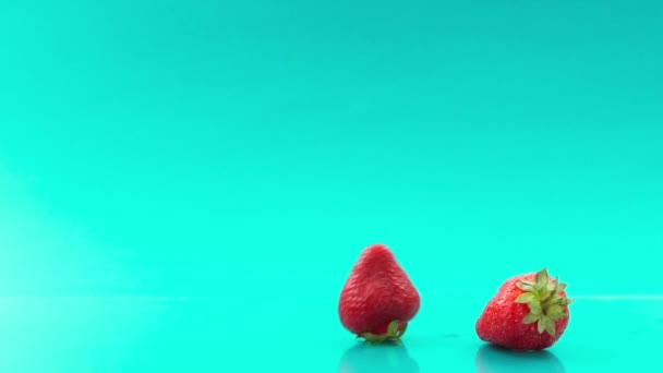 rolling strawberry one after one on turquoise background