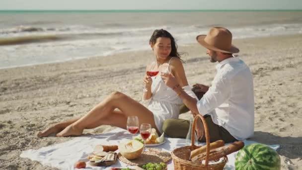 krásný krásný pár slaví s vínem a povzbuzující sklenice vína na letním plážovém pikniku. veselí lidé cinkání sklenice na víno a líbání
