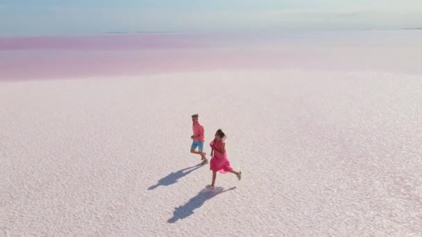 Aerial drone footage of happy young couple in pink wear having fun and joyfully running on white coast of bright colorful pink mineral lake