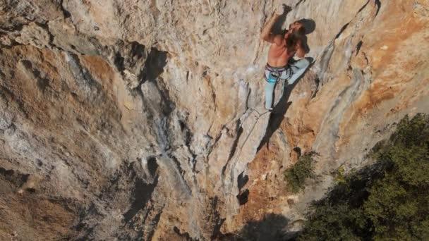 Aus der Vogelperspektive erklimmt ein kräftiger muskulöser Mann eine anspruchsvolle Kletterroute. Bergsteiger greift nach Griffen und macht lange, harte Bewegungen